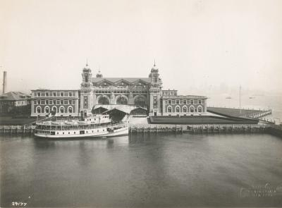 A black and white picture of the Ellis island immigration station from the front view with a boat docked in front of it